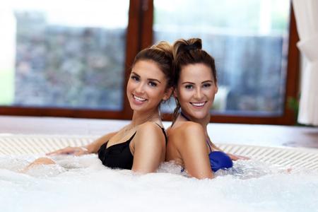 Happy girl friends enjoying jacuzzi in hotel spa Stock Photo