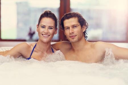 Happy couple enjoying jacuzzi in hotel spa Imagens