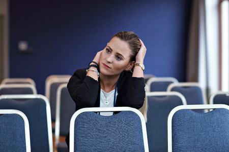 Young woman sitting alone in conference room Stok Fotoğraf