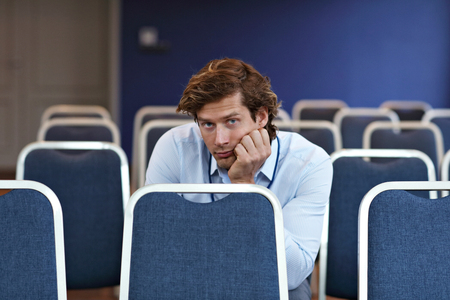 Young man sitting alone in conference room Stok Fotoğraf - 90910420