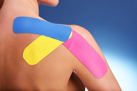 Picture showing special physio tape put on injured arm over white background