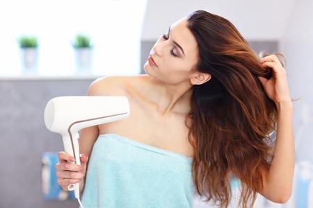 Jeune femme à l'aide d'un sèche-cheveux dans la salle de bain le matin Banque d'images