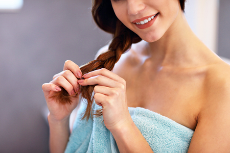 Jonge vrouw die zich in badkamers bevindt en haar borstelt