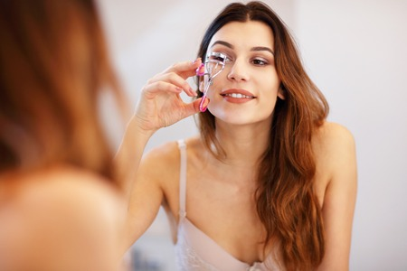 Attractive young woman doing make-up while looking at the mirror in bathroom