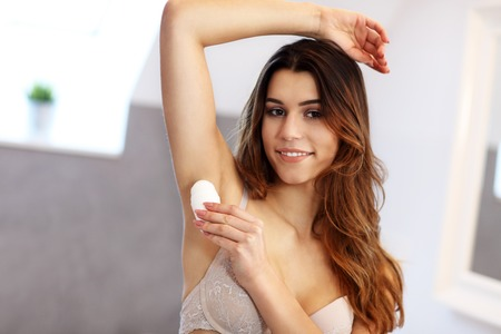 Woman applying deodorant on armpit in bathroom