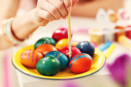 Attractive woman painting Easter eggs at home Stock Photo