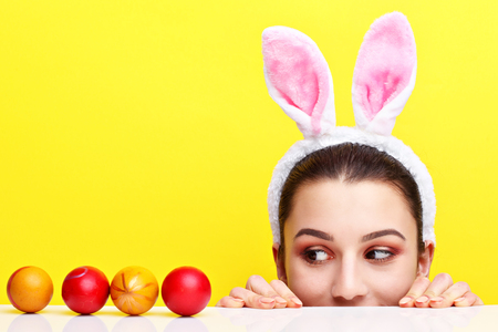 Happy young woman wearing bunny ears and having Easter Eggs Stock Photo