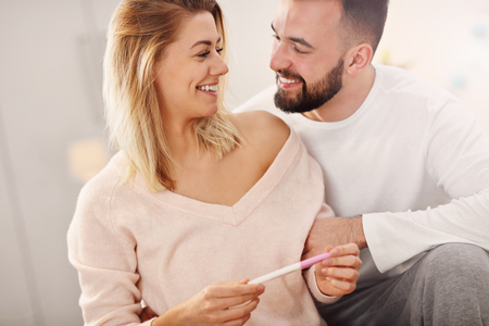 Happy couple with pregnancy test in bedroom