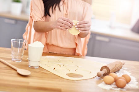 Young woman trying to make pierogi in kitchen
