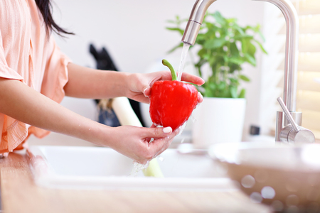 Young woman washing red bell pepper in modern kitchen