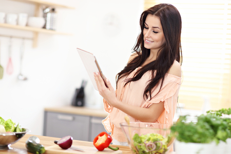 Happy woman preparing salad in modern kitchen and holding tablet