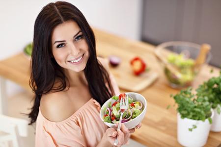 Happy woman preparing salad in modern kitchen