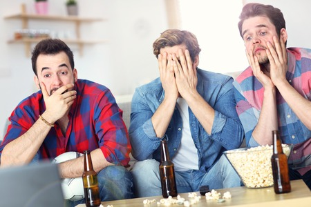 Sad male group of friends watching sports on tv at home Stockfoto