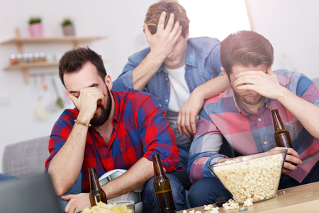 Sad male group of friends watching sports on tv at home Stock Photo