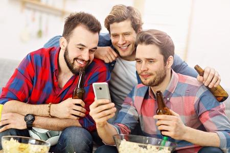 Happy male friends cheering and watching sports on tv Zdjęcie Seryjne