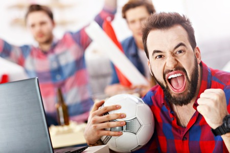 Happy male friends cheering and watching sports on tv Stock Photo