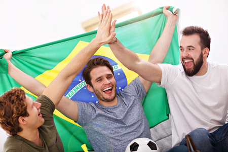 Happy male friends cheering and watching sports on tv Stockfoto