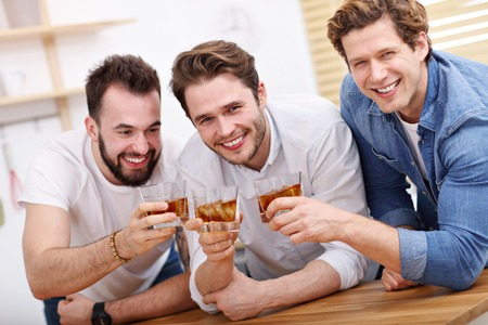 Cheerful friends having fun with smartphone and drinking at home
