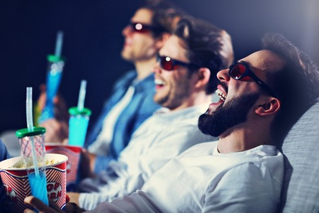 Grupo de amigos felices sentados en la sala de cine cine y comiendo palomitas de maíz Foto de archivo - 99040451