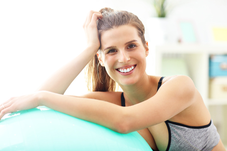Woman doing fitness exercises at home resting on ball