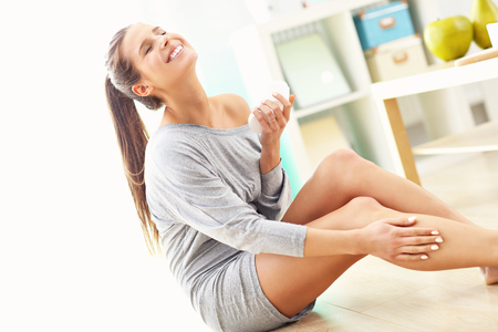 Woman using body lotion on her legs