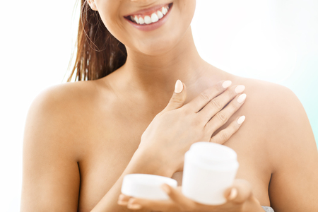 Woman using body lotion on her skin Stock Photo