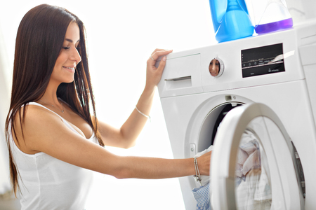 Picture of young housewife with laundry next to washing machine