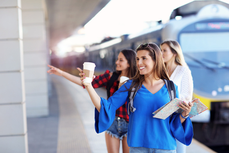 Group of girl friends tourists on railway platform