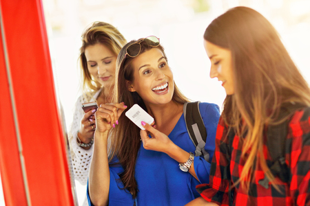 Group of girl friends tourists on railway platform with ticket