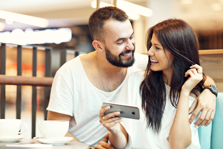 Romantic couple dating in cafe and using smartphone Foto de archivo