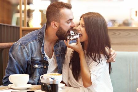 Romantisches Paar, das im Café datiert und Donut isst Standard-Bild
