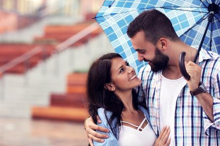 Happy couple under umbrella in the city Stock Photo