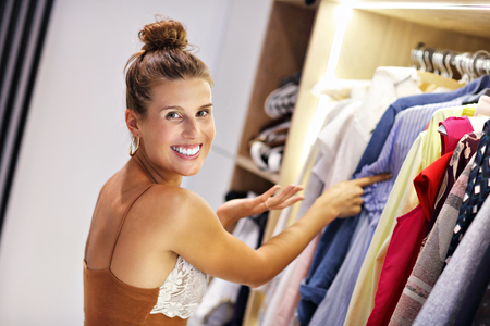 Beautiful woman thinking what to dress in walk-in closet