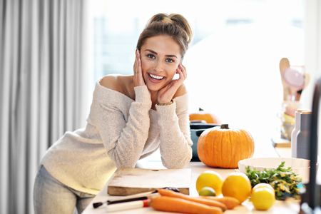 Adult woman in the kitchen preparing pumpkin dishes for Halloween
