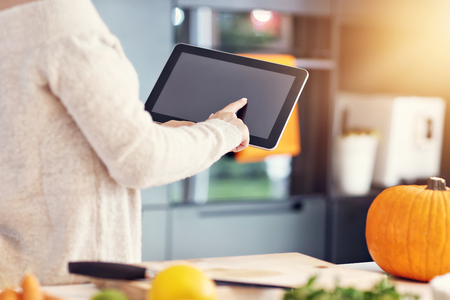 Midsection of adult woman in the kitchen preparing pumpkin dishes for Halloween