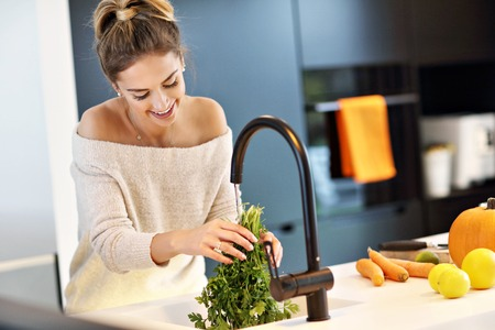 Adult woman washing parsley in the kitchen
