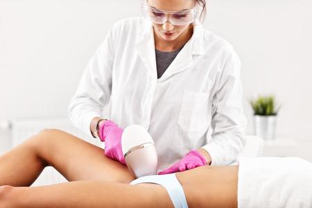 Donna adulta che ha epilazione laser nel salone di bellezza professionale
