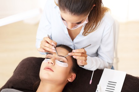 Adult woman having eyelash extension in professional beauty salon