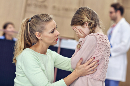Little girl is crying while with her mother at a doctor on consultation