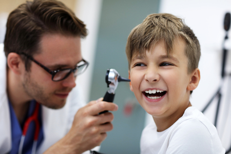 Close-up Of Male Doctor Examining Boys Ear With An Otoscope