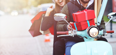 Portrait of happy couple with shopping bags after shopping in city smiling and huging