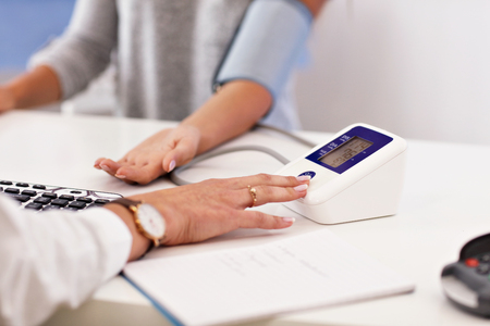 Adult woman having blood pressure test during visit at female doctors office Stock Photo