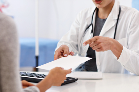 Adult woman having a visit at female doctors office Stock Photo