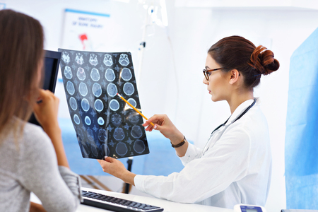 Adult woman discussing x-ray results during visit at female doctors office