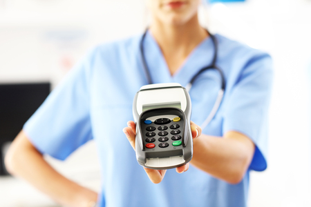 Female doctor standing in her office with payment terminal