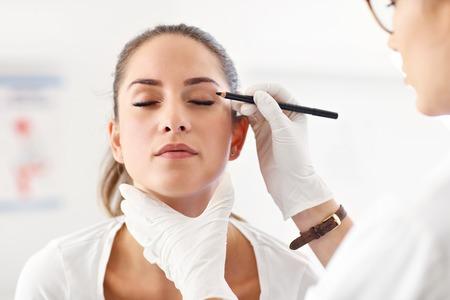 Plastic surgeon making marks on patients body Stock fotó