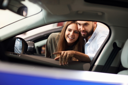 Adult couple choosing new car in showroom