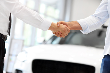 Midsection of young couple buying new car