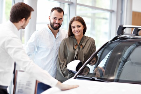 Confident young salesman explaining car features to the young attractive owners 스톡 콘텐츠