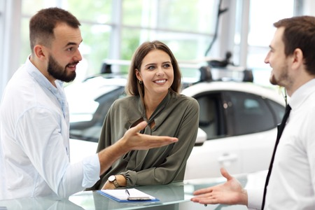 Confident young salesman explaining car features to the young attractive owners Фото со стока